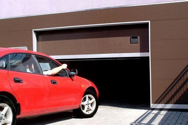 На фото электропривод для гаражных ворот в действии. Он обеспечивает открывание ворот нажатием одной кнопки.
