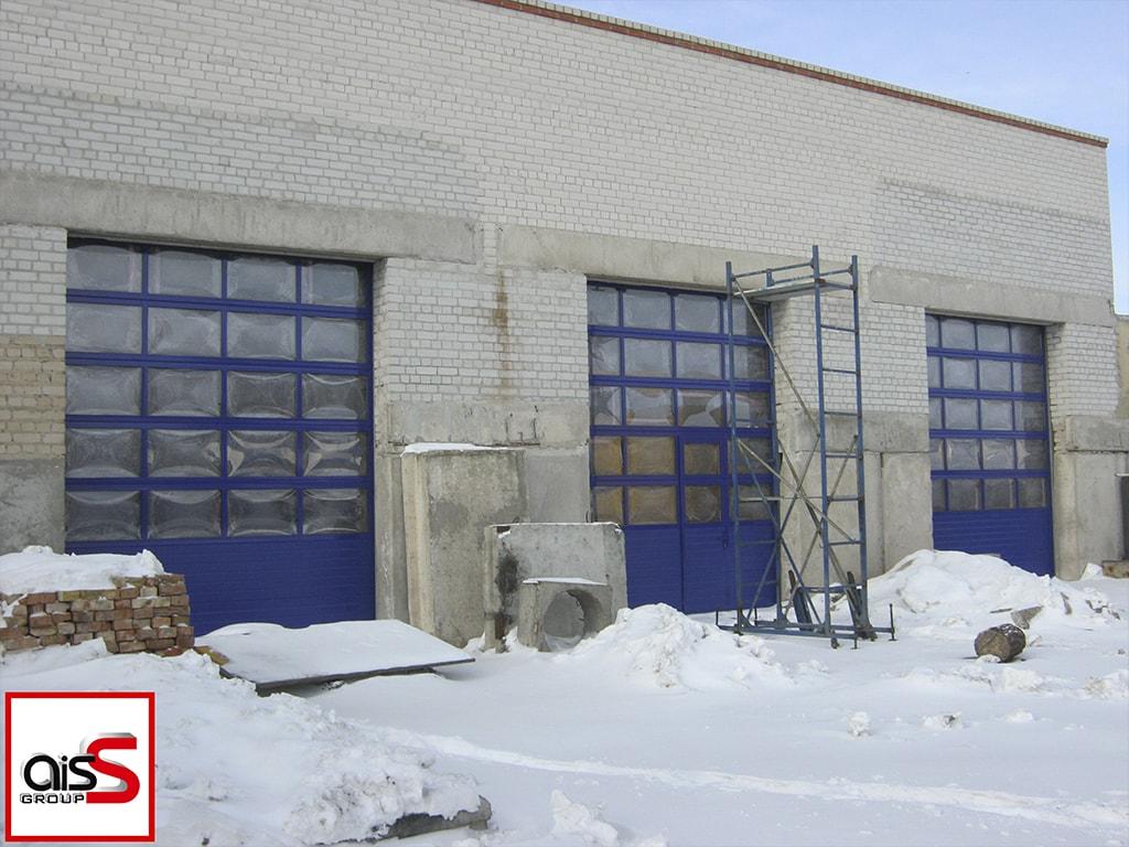 Промышленные панорамные ворота в стильном синем цвете на фото.