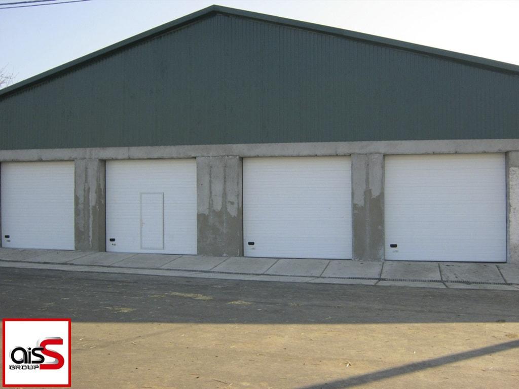 Белоснежные секционные ворота для промышленных объектов на фото.
