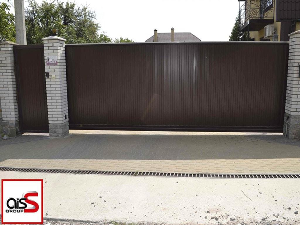 Откатные ворота в частный дом из профнастила с отдельностоящей калиткой на фото.
