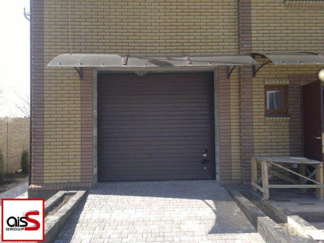 Стандартные секционные ворота под навесом на фото.