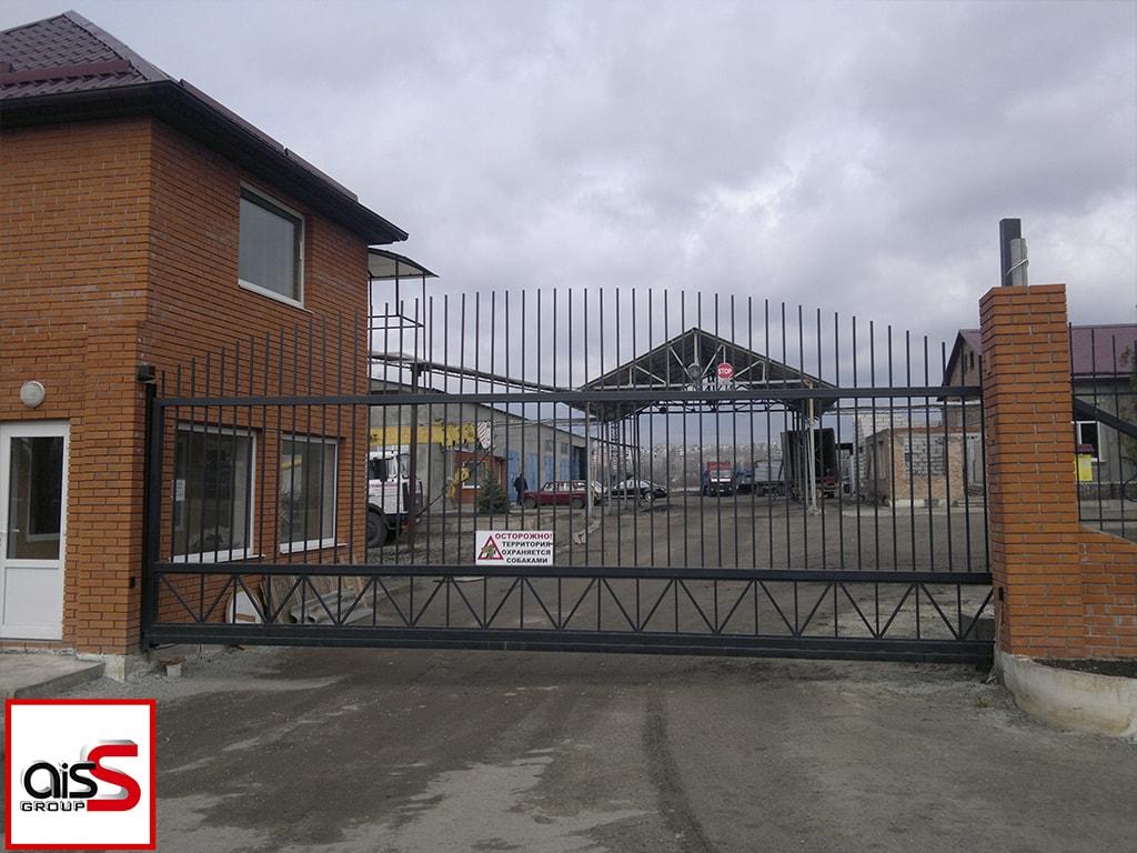 Кованые откатные ворота для автопарка в черном цвете на фото.