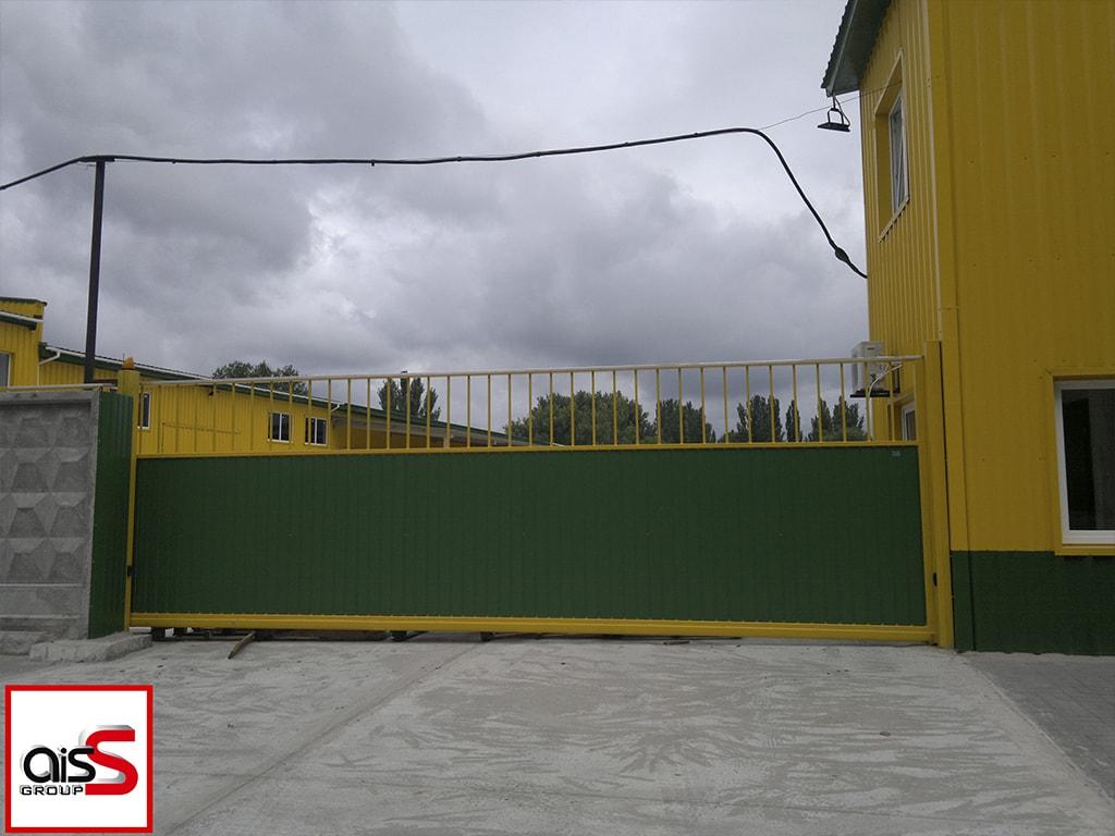 Промышленные откатные ворота с элементами ковки и зашивкой из профнастила на фото.
