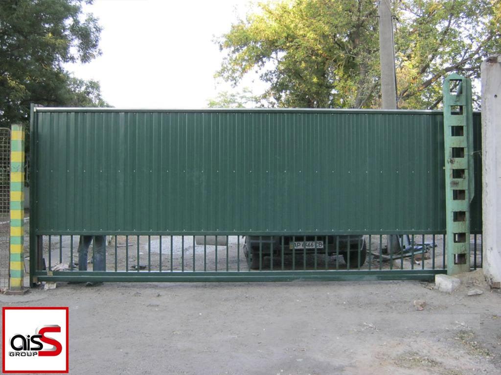 На фото промышленные откатные ворота из профнастила с элементами ковки.