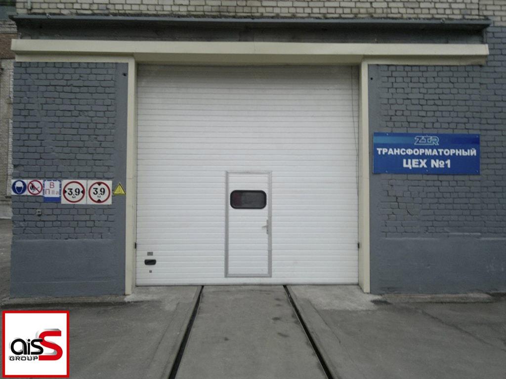 Промышленные секционные ворота с высоким подъемом и калиткой на фото.
