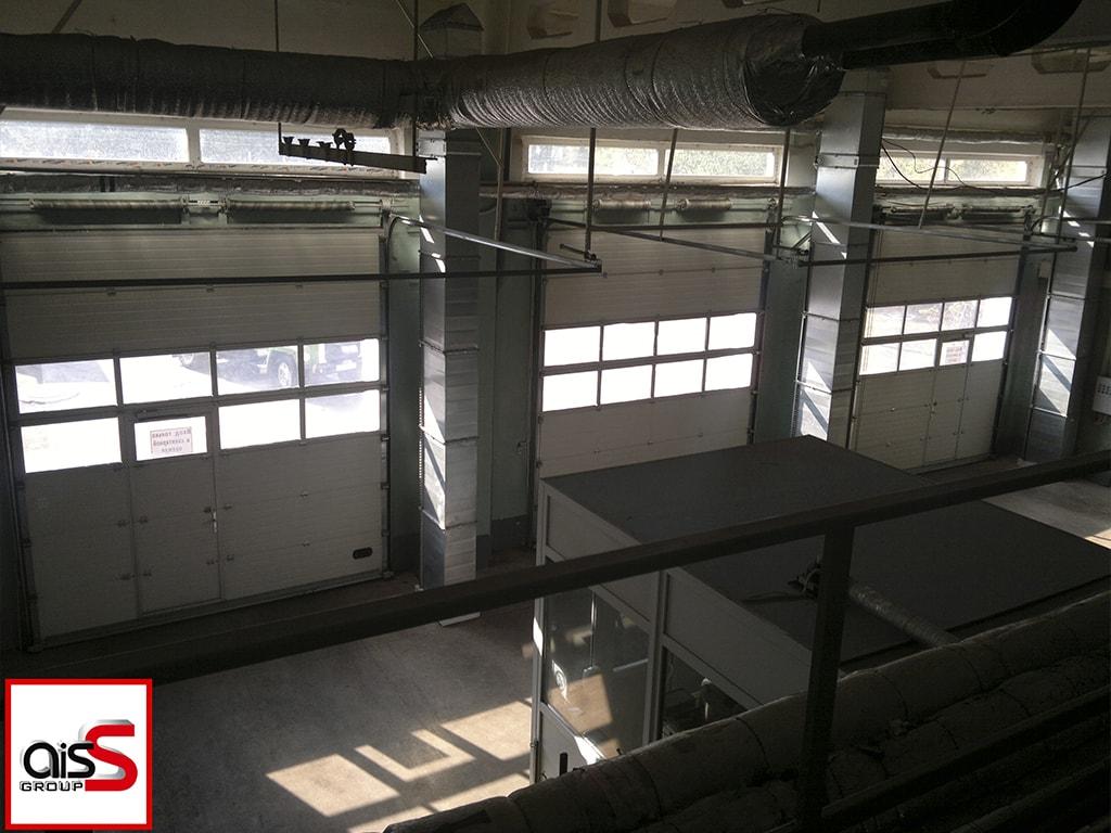 Подъемные промышленные ворота с прозрачными вставками и калитками на фото.