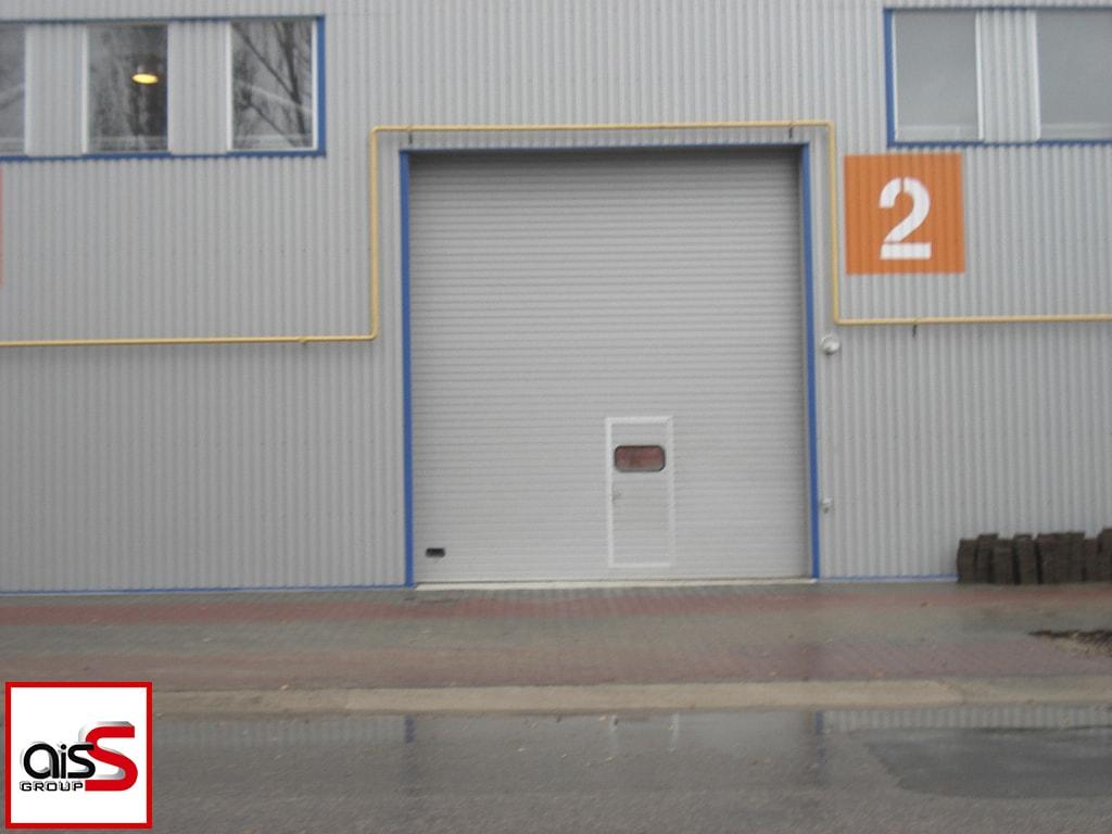 На фото секционные ворота с повышенным подъемом и встроенной калиткой.
