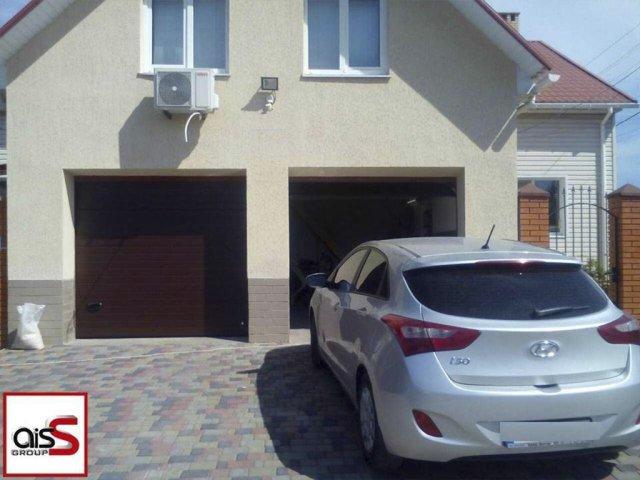Двойные гаражные ворота секционного типа на фото частного дома.