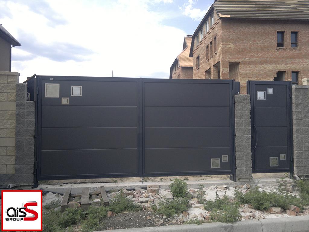 Комплект распашные ворота и калитка в едином стиле. Ворота зашиты сендвич панелями Ритерна, тп панелей MidRib (широкая полоса) цвет серый.