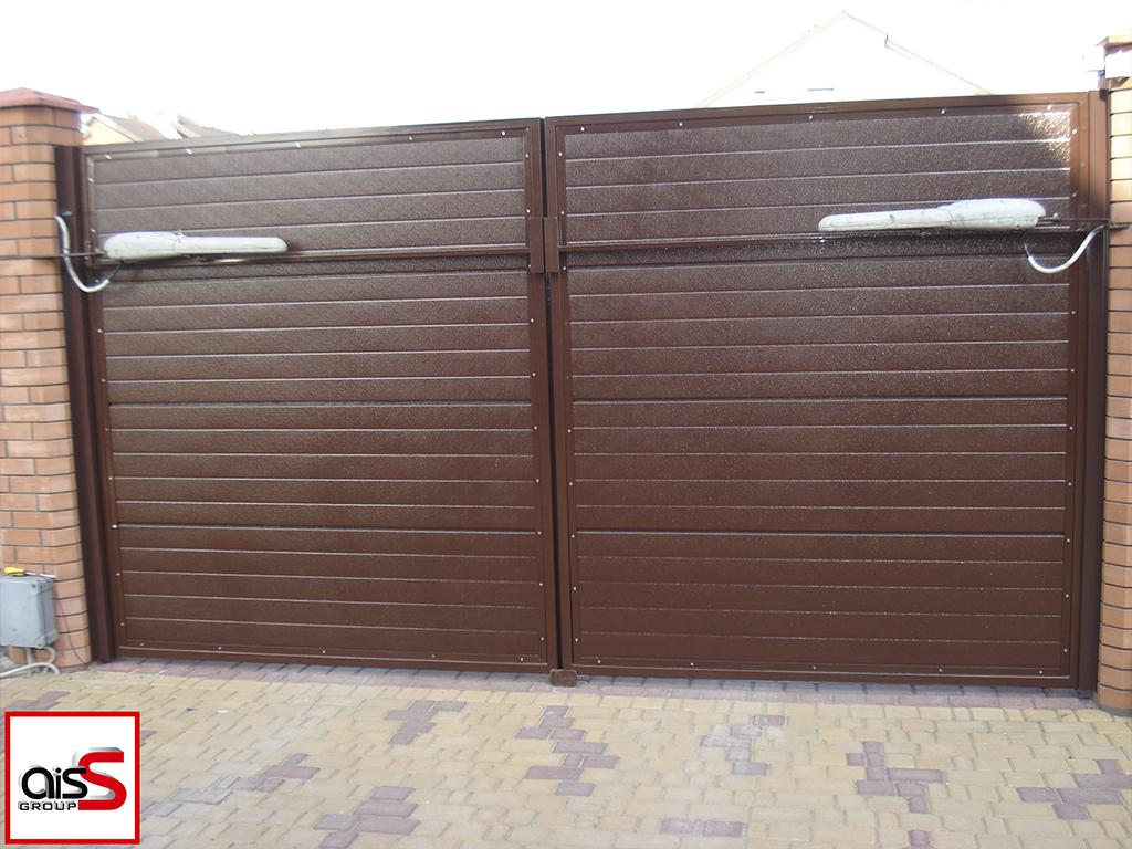 Автоматические распашные ворота в частном доме. Ворота зашиты панелями Ритерна тип гофр цвет коричневый.