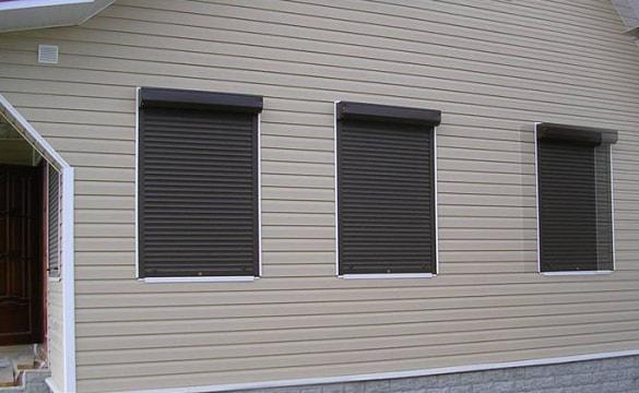 Фотография защитных роллет на окна. Выполнены из алюминиевого профиля в черном цвете.